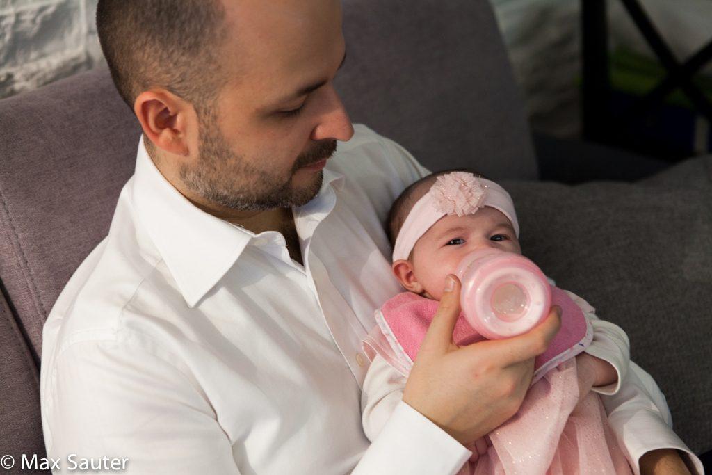 Bébé prend le biberon dans les bras de papa